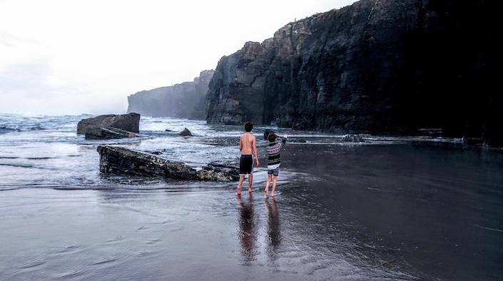 Boys walking on foggy beach