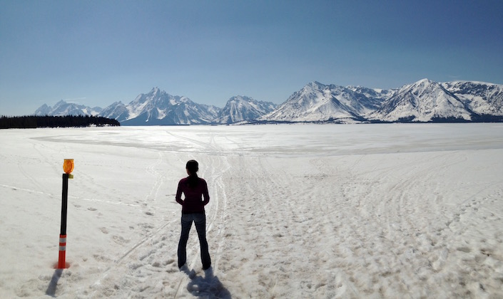 Me looking at a frozen lake with a lot of foot prints in snow