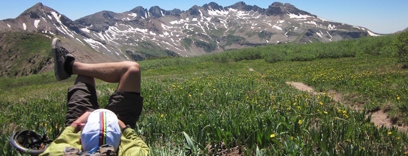 mountain biker laying down in mountain meadow