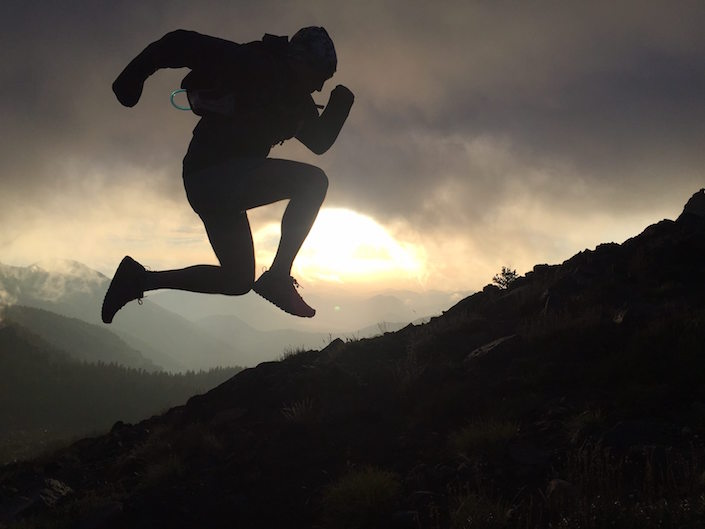 Hiker jumping. Mountain sunrise.
