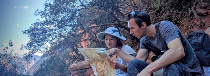 Two people looking at a map in a canyon