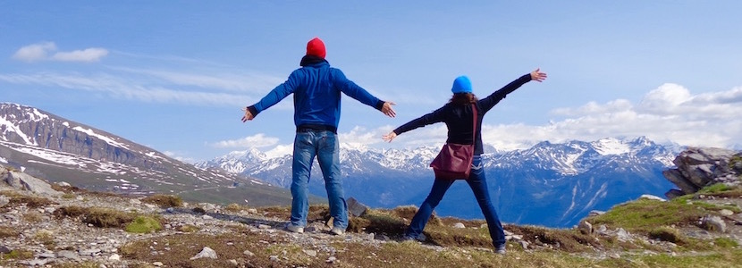 Two people in mountains (arms up, facing the view)