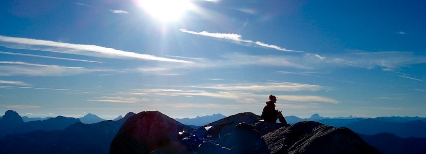 mountain climber sitting on peak looking out over mountain range