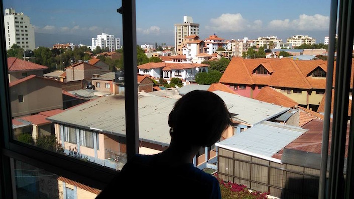 child looking out window over Cochabamba