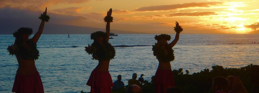 hula dancers in front of a sunset