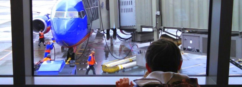 kid looking out window at plane