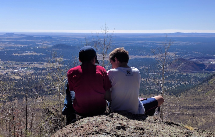 two boys sitting on rock overlooking forest/town
