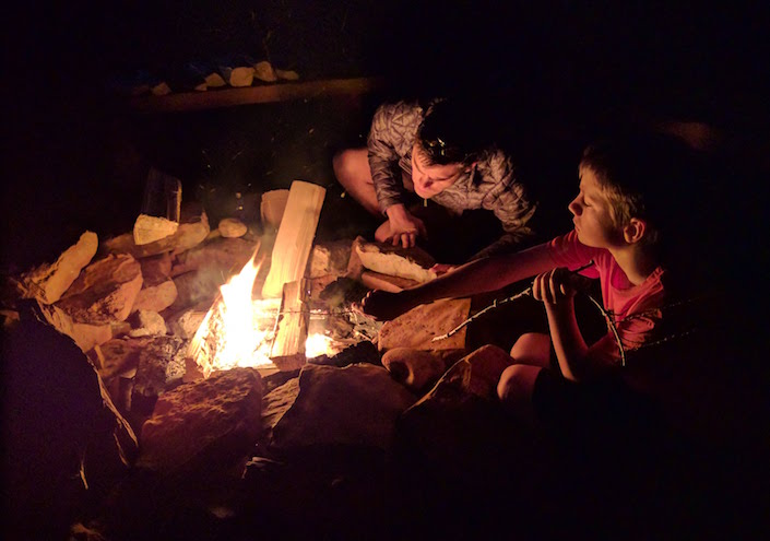 adult and child tending campfire