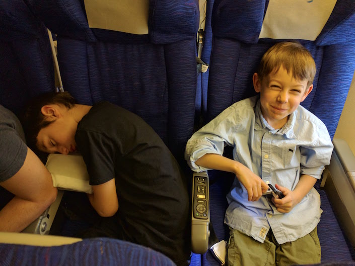 kids on plane - one asleep, one smiling