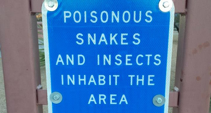 "Sign: ""Poisonous snakes and insects inhabit the area"""