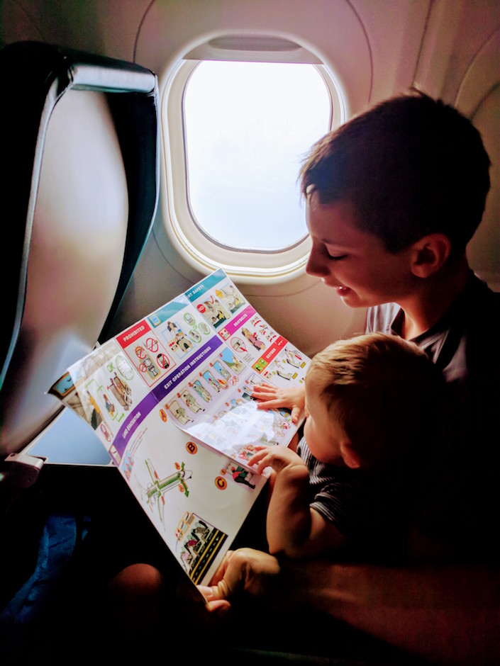kids on airplane looking at safety card.