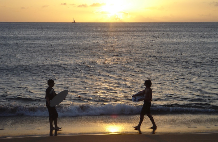 kids with boogie boards in sunset