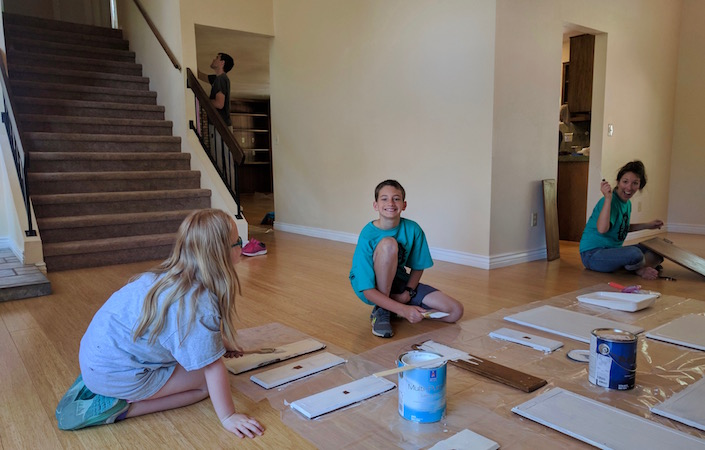 Kids painting cabinet doors.