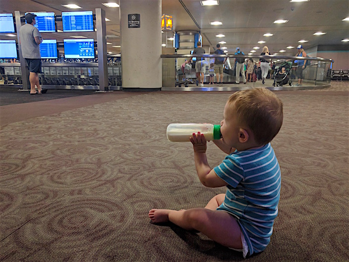 Baby eating bottle in airport watching traveler check arrivals board