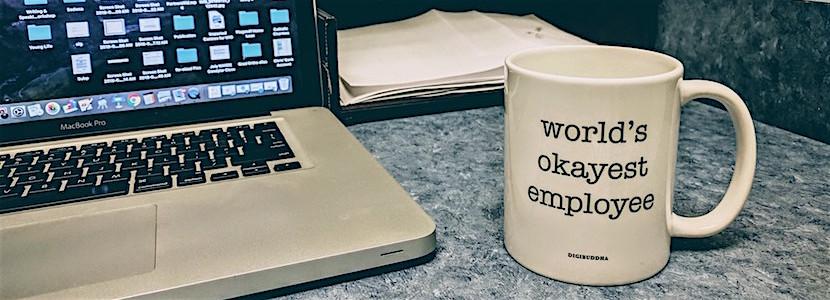 """world's okayest employee"" mug by laptop"