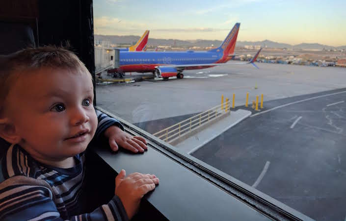 baby next to window at airport with planes