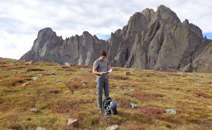 Man in mountain wilderness with backpack reading guidebook