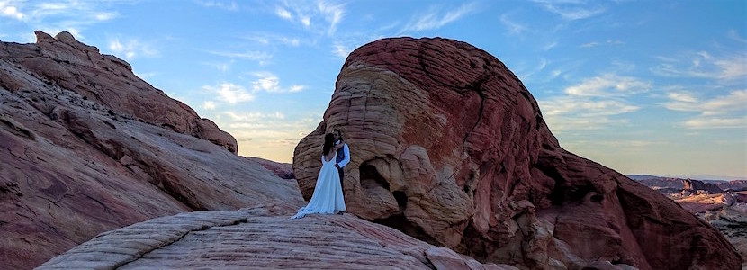 bride and groom on rock rocks during sunset