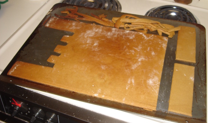 Giant gingerbread dough cut-outs on baking sheet
