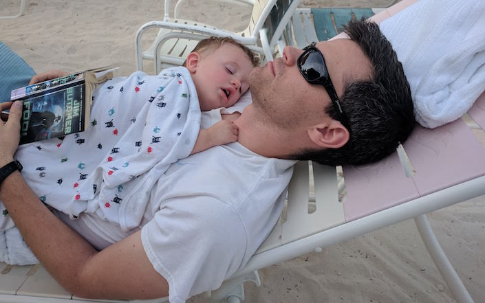 man asleep on lounge chair with book - baby asleep on his chest