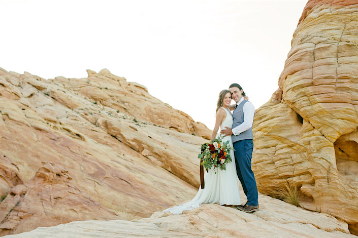 bride and groom on red rocks smiling at camera