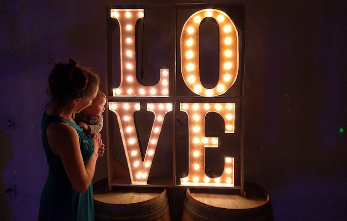 "mom and baby in front of ""love"" sign on top of barrels"