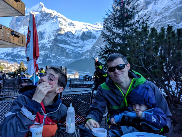 One kid showing off his bruised face and one kid eating fries. Mountain background.