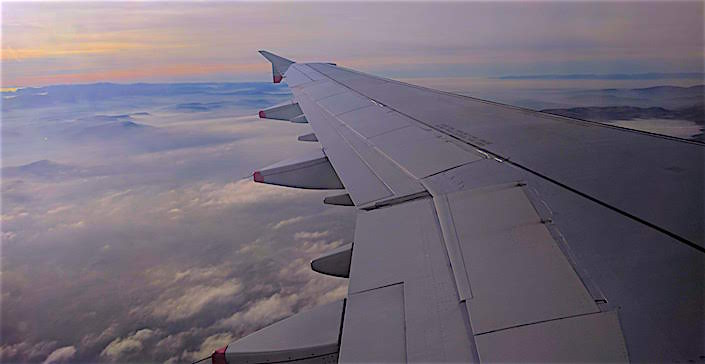 plane wing with cloudy sunset