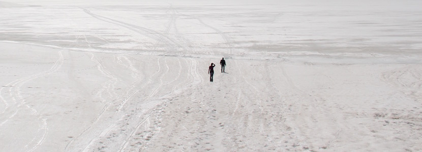 two people in the middle of a snow field
