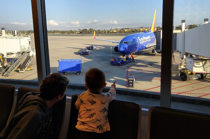 two kids looking at a parked plane