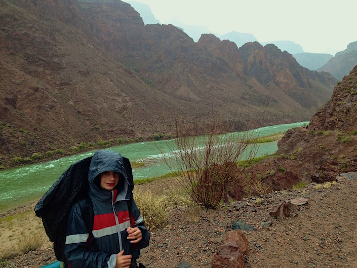 tween backpacking in rain gear by river