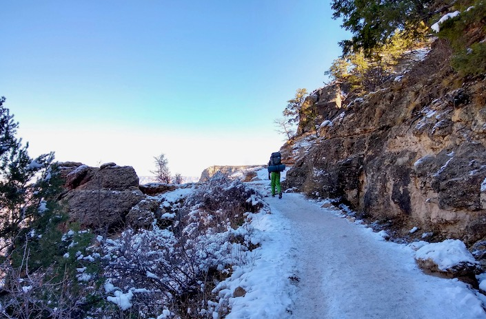 teen backpacker hiking on icy trail