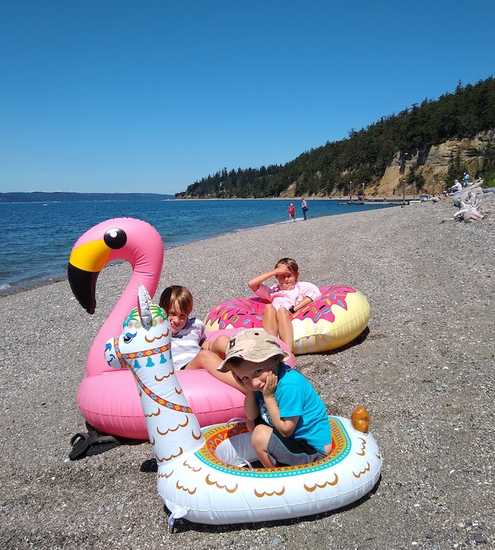 kids on floaties sitting on shore